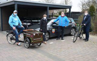 Vier Personen stehen vor einem Auto oder sitzen auf einem Lastenrad.