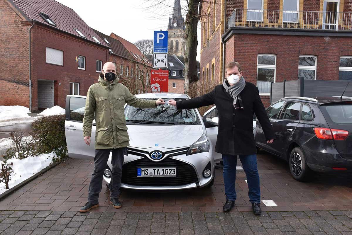 Bürgermeister Thomas Stohldreier nimmt den Autoschlüssel von Till Ammann, Geschäftsführer von Stadtteilauto, entgegen