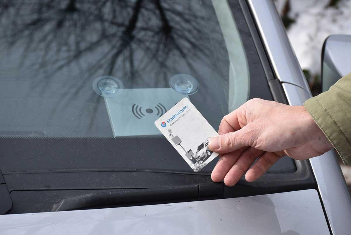 Eine Hand mit einer Chipkarte vor einer Frontscheibe eines Autos.