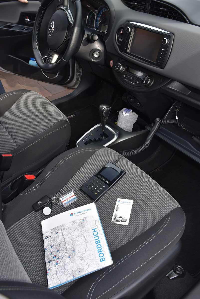 Innenansicht des Stadteilautos. Der Beifahrersitz mit Bordbuch.