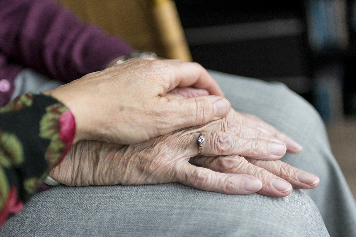 Zwei Hände in der Nahaufnahme. Eine jüngere Hand liegt auf einer älteren Hand.