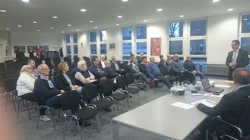 Foto der IKEK-Versammlung. Ansicht einer Gruppe von Menschen mit einem Redner.