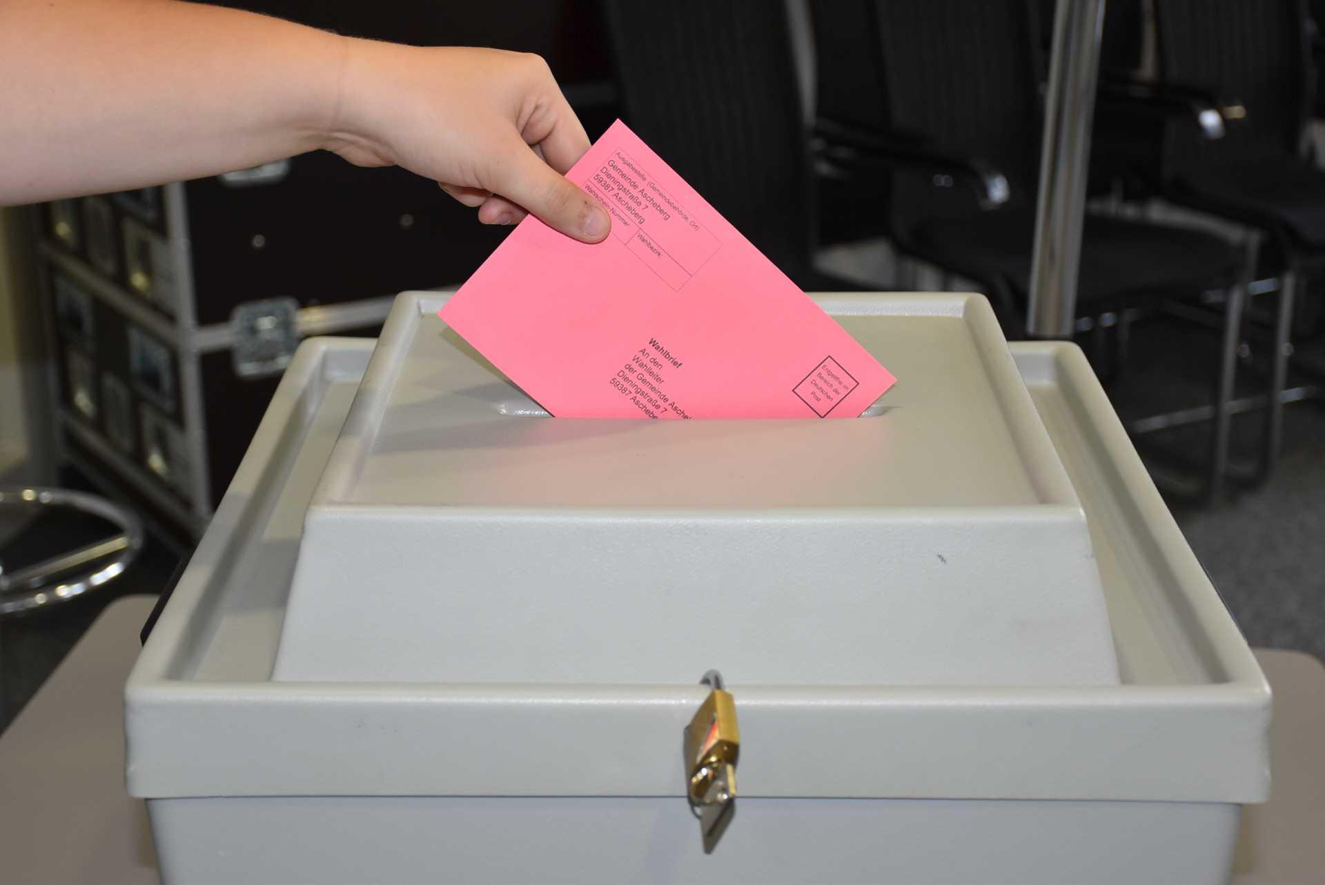 Briefwahlumschlag wird in Wahlurne geworfen